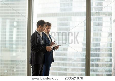 Busy company leader giving instructions to assistant, explaining work cases to new employee, discussing perspectives and project ideas with business partner while walking near large window in office
