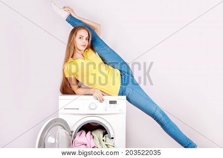 Young beautiful woman in blue jeans sits on a washing machine lifting her leg in a twine, isolated on a white background