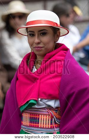 June 17 2017 Pujili Ecuador: indigenous female in colorful dress wearing a white hat at the Corpus Christi parade