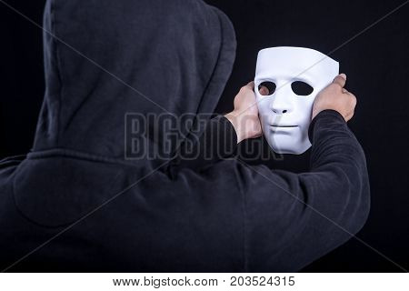 Mystery man holding and looking at white mask. Anonymous social masking or halloween concept.