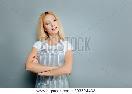 Let me look. Delighted blonde crossing arms on chest and keeping smile on face while standing isolated on grey background