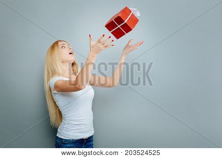 I am surprised. Concentrated young woman keeping mouth opened and raising arms while standing in semi position over grey background