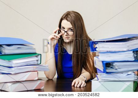 Young Beautiful Girl In Glasses And Blue Dress Is Sitting In The Office At The Table With A Lot Of F