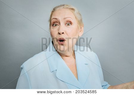 Active mimic. Positive female person opening mouth and looking at camera while standing over grey background