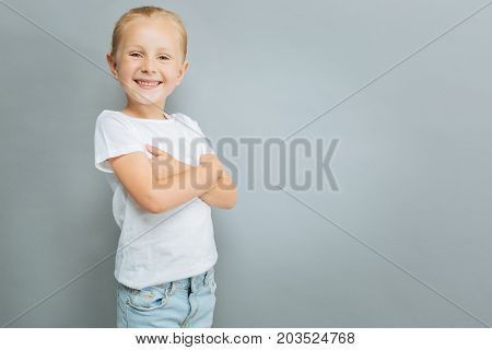 Friendly smile. Positive delighted child standing in semi position and feeling happiness while looking at camera