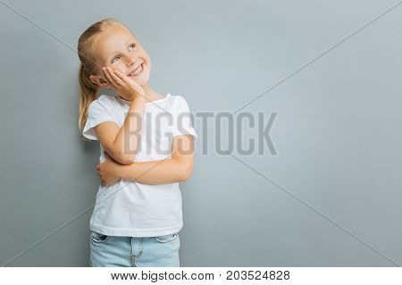 I am pleased. Positive delighted kid keeping smile on her face and leaning head on right hand while standing over grey background