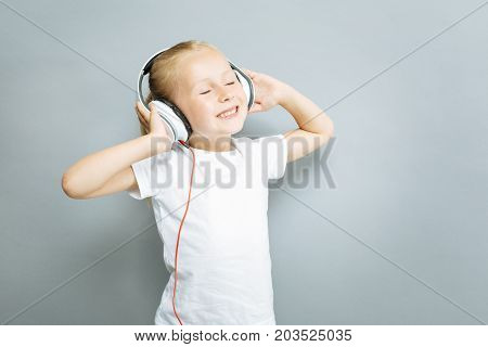Enjoy the moment. Delighted blonde girl keeping eyes closed and putting hands on the headphones while standing in semi position over grey background