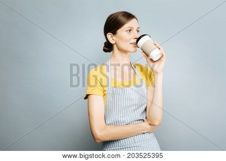 Time for coffee. Amazing girl standing in semi position and looking sideways while putting right arm on the chest, isolated on grey