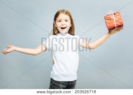 Amazing day. Delighted girl opening mouth and holding red box with present in left hand while looking at camera with wide opened eyes