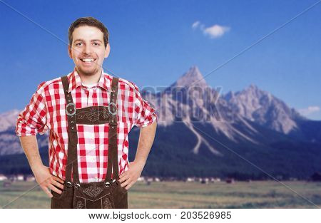 Laughing bavarian man with leather pants is ready for the oktoberfest and mountains in the background