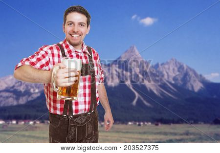 Laughing bavarian oktoberfest guest with leather pants and beer mug and mountains in the background