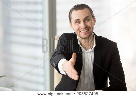 Portrait of friendly smiling businessman offering hand for greeting or agreement handshake in modern office setting. Business person looking at the camera. Successful deal, self-introduction concept