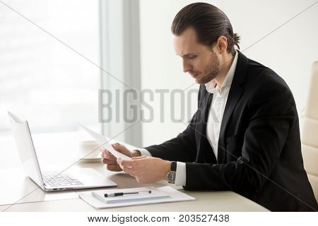 Serious businessman reading important financial document at workplace in modern office. Laptop, notes, cup of coffee on the table. Concerning news, unexpected bill, debt, letter of refusal concept.