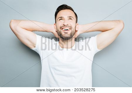 Thanks God. Positive delighted bearded man raising arms and keeping smile on face while looking upwards