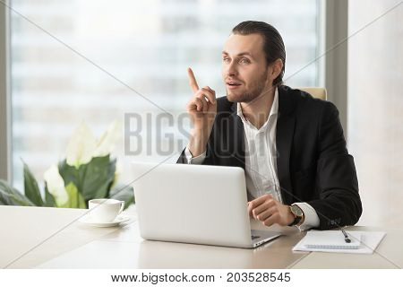 Project manager sitting in front of laptop with forefinger raised up. Young entrepreneur suddenly got great idea at work desk. Successful businessman found great solution. Brainstorming success.