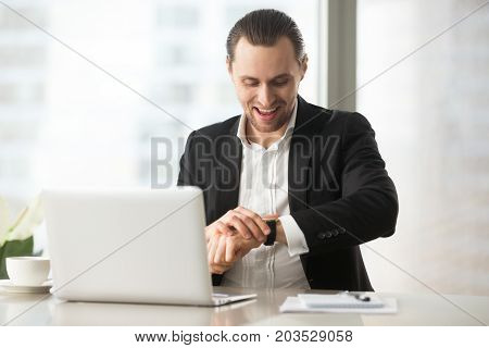 Cheerful businessman at work looking at wristwatch with big smile. Manager ready to leave the office. Entrepreneur or CEO happy about work day being over, being done with project on time concept.