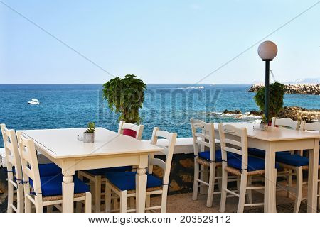 A covered table in a Greek tavern and a sea. Summer background for travel and holidays.