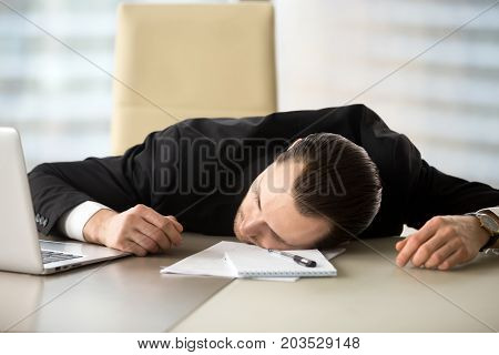 Exhausted businessman passed out at workplace desk in office. Tired entrepreneur laying on his desk in front of laptop and notes. Fatigued office employee fell asleep during work hours. Too much work