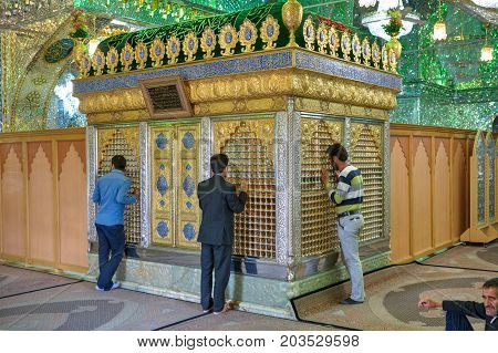 Fars Province Shiraz Iran - 18 april 2017: Mirrored mausoleum in Sayyed Alaeddin Hossein Mosque Iranian men worship an Islamic shrine.