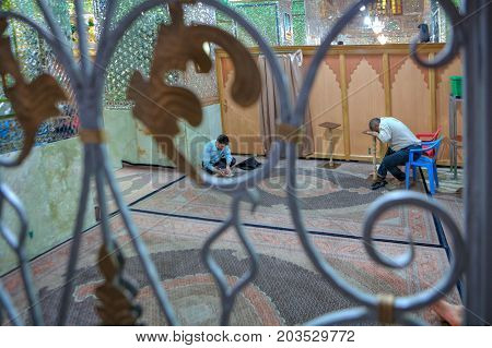 Fars Province Shiraz Iran - 18 april 2017: Muslim Shiite Men praying inside mirrored Mosque of Sayyed Alaeddin Hossein.