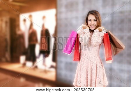 cheerful young asian woman happy smiling holding shopping bag while standing at brand name clothes shop in department store shopping mall online payment shopping online lifestyle technology concept