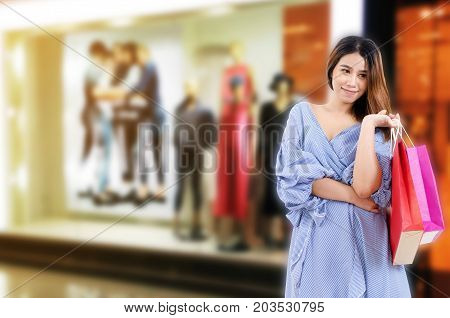 cheerful young asian woman holding shopping bags while standing at brand name clothes shop in department store shopping mall online payment shopping online lifestyle technology concept