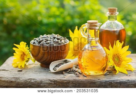 Sunflower oil with flowers and seeds on old table. Outdoors