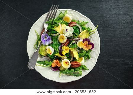 Healthy summer salad with quail eggs, avocado, pecans, wild rocket, red onion and edible viola flowers