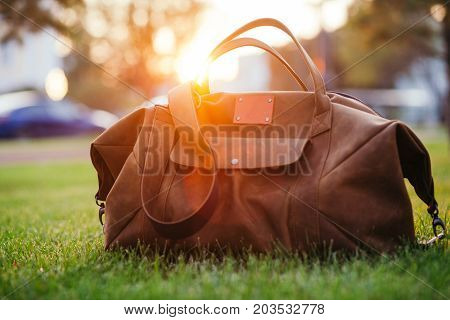 Retro brown shoes and man leather bag in bright colorful summer grass in the park.