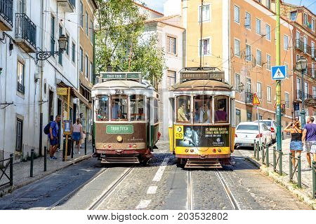 Lisbon, Portugal - August 25, 2017: Two trams in Lisbon: new Tram Tour and famous historic yellow Tram 28 on the narrow streets of Alfama. Trams are icon of the Portuguese capital. Lisbon urban view.
