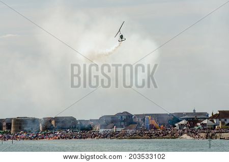 Clacton Essex United Kingdom -25 August 2017: Gyro copter flying over Clacton Essex in annual free air display with crowd in background