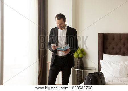 Businessman holds guide brochure and calls taxi or room service from hotel apartment. Business traveler reading information, looking up address, ordering dinner delivery. Trip or vacation concept.