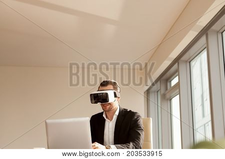 Smiling businessman in vr headset testing app on laptop. Office worker or CEO immersed in virtual reality, innovative method of browsing web or managing business project through augmented reality.