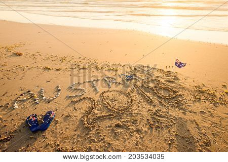 Australia 2018 text with thongs and sunglasses on beach at sunset