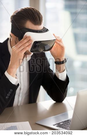 Businessman wears vr headset, immersed in virtual reality looking at laptop screen. Young office worker, entrepreneur using innovative technology, tests new applications, manages business projects.