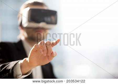 Businessman in VR glasses pointing finger in air. Office worker or CEO immersed in virtual reality, innovative method of managing business project through augmented reality. Close up. Space for text.
