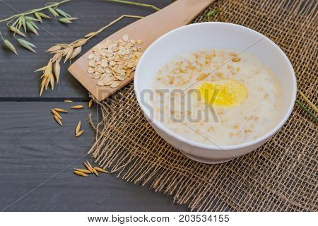 Porridge from oat flakes in a white dish, healthy Breakfast, on wooden table,  with natural grain, spikelets and cereals oats, closeup