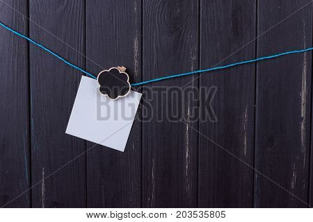 Clothespins papers with a place for inscription on a black wooden background