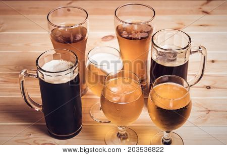 Beer glasses and beer mugs on wooden table. Selective focus. Vintage style