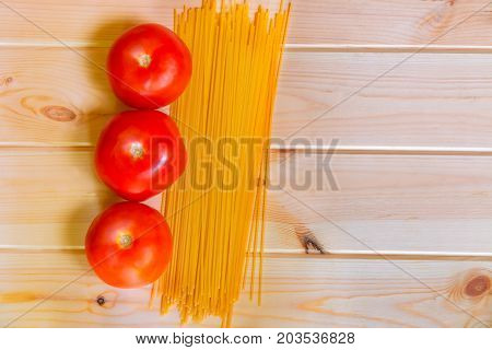 Spaghetti pasta with fresh tomatoes on wooden background