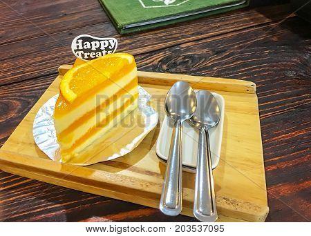 Orange cake on wood plate on wood table