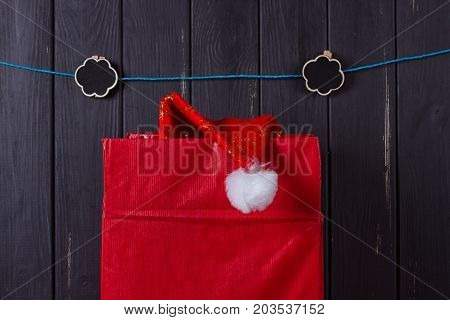 large red box from which the cap of Santa Claus sticks out against the background of a wooden black fence. Christmas