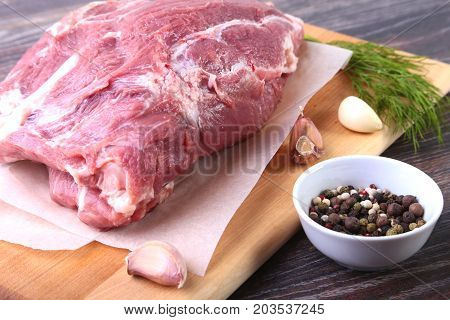 Raw pork steaks on wooden board with herbs, garlic and spices ready for cooking. Selective focus