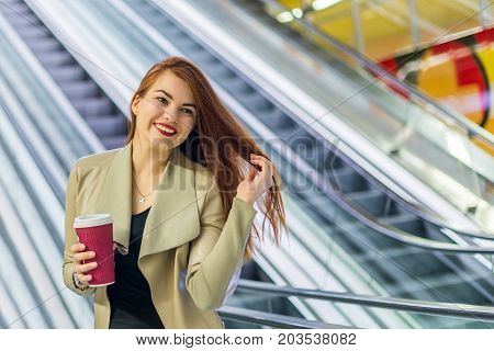 The girl smiling and holding mug of coffee near escalator at the subway