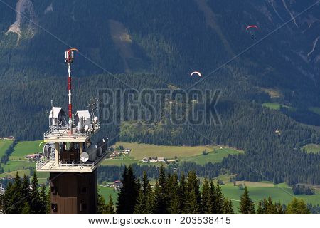 Planai Telecommunication Tower With Flying Paragliders In Background