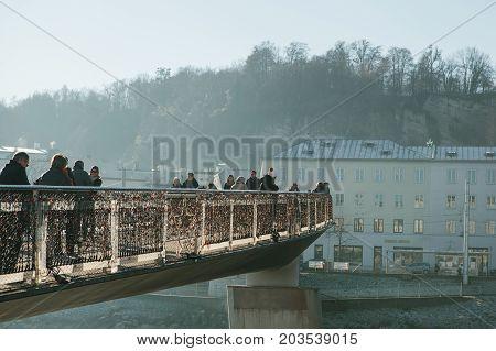 Austria, Salzburg, January 1, 2017: Mozart's Pedestrian Bridge is located in Salzburg and is a pedestrian bridge connecting the Old and New Pedestrians walk on the bridge.