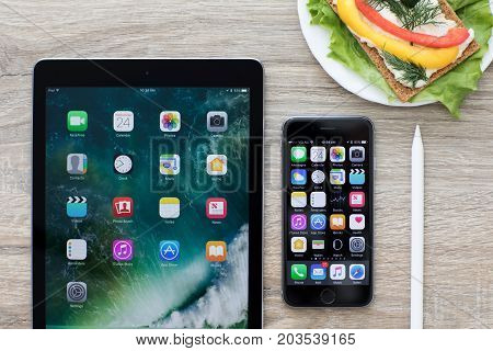 Alushta Russia - May 24 2017: iPad Pro and iPhone with home screen in the table. iPad Pro and iPhone was created and developed by the Apple inc.