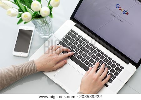 Alushta Russia - May 26 2017: Woman hand MacBook Pro with social networking service Google on the screen. MacBook was created and developed by the Apple inc.