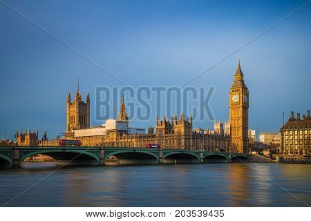 London England - Traditional red double decker buses on Westminster Bridge with Big Ben and Houses of Parliament at sunrise