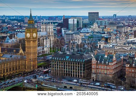 London England - Aerial skyline view of the famous Big Ben with Houses of Parliament St Margaret Church with red double decker buses at sunset